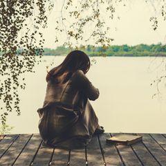 Horoskop: Eine traurige Frau am See