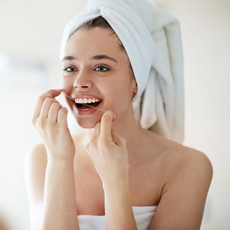 Zahnseide: Frau benutzt Zahnseide im Bad