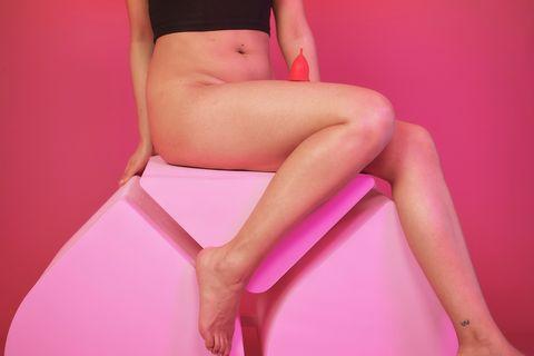 Frau mit nacktem Unterkörper und Menstruationstasse