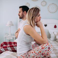 Frust mit Männern: Ein frustriertes Paar sitzt nebeneinander auf dem Bett