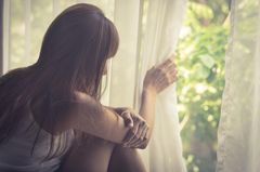 Was kann ich aus einer Krise lernen? Eine traurige Frau schaut durch einen Vorhang nach draußen