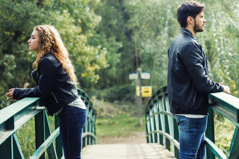 Whisper: Ein Paar steht auf einer Brücke und schaut in unterschiedliche Richtungen