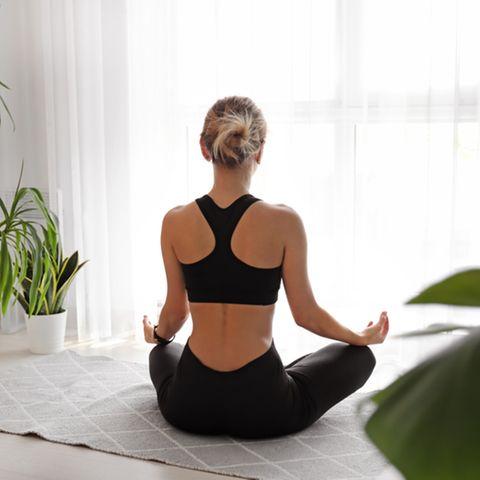 Meditationsraum: Frau meditiert sitzend auf dem Boden