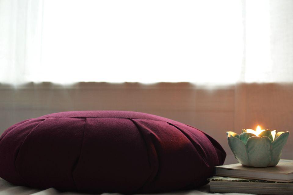 Meditationsraum: Meditationskissen und eine Kerze