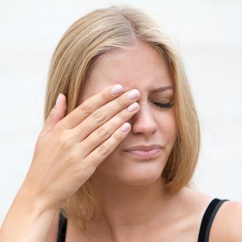 Brennende Augen: junge Frau, Augenschmerzen, Schmerzen im Gesicht
