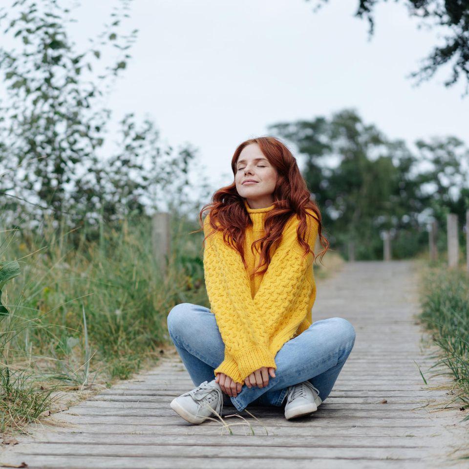 Wovor braucht man keine Angst zu haben? Eine rothaarige Frau sitzt mit geschlossenen Augen am Strand