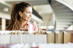 Duales Studium, klassische Uni oder Ausbildung?: Junge Frau vor Bücherregal