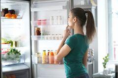 Kühlschrank Temperatur: Frau steht vor offenem Kühlschrank