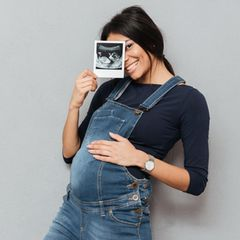 Schwangere mit Ultraschallbild in der Hand