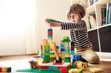 Fläschchen-Mütter: Kind spielt mit Bauklötzen