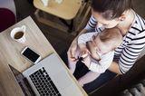 Fläschchen-Mütter: Frau mit Baby auf dem Schoß am Schreibtisch