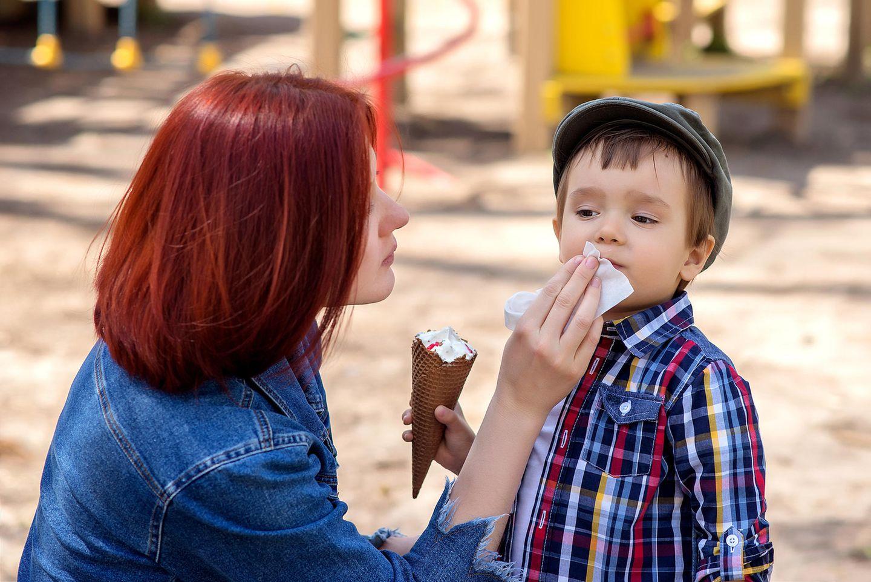 Freundschaft unter Müttern: Mutter wischt den Mund ihres Sohnes sauber