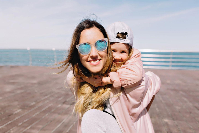 Freundschaft unter Müttern: Mutter mit Tochter auf dem Rücken