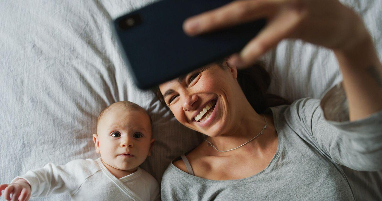 Freundschaft unter Müttern: Mutter fotografiert sich und ihr Baby mit Smartphone