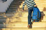 Vereinbarkeit: Junge geht Treppe hoch und trägt seine Schultasche