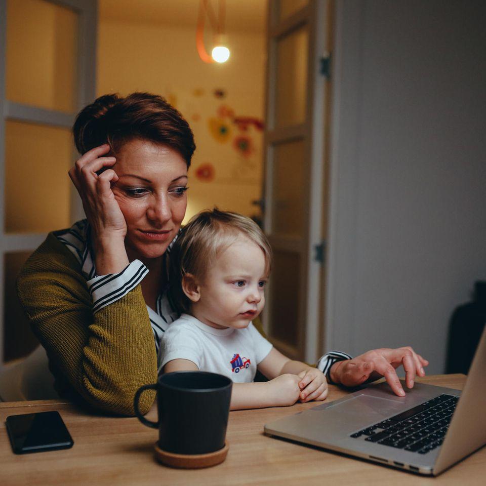 Vereinbarkeit: Frau mit Kind auf dem Schoß am Laptop