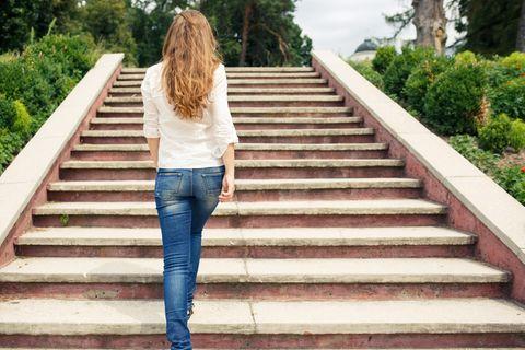 Erfolgsgeheimnis: Eine erfolgreiche Frau geht eine Treppe hinauf