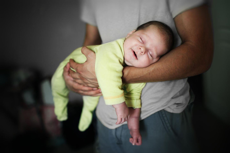 Einschlafritual Stillen: Baby schläft in Papas Arm