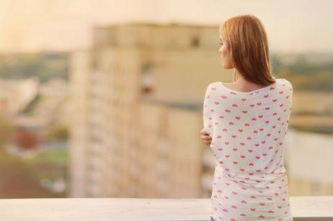 Unsicherheit: Eine einsame Frau auf einem Dach