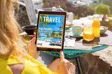 Sommer 2020: Frau mit Reisemagazin auf Tablet