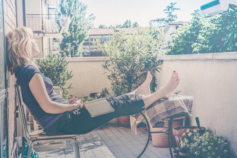 Sommer 2020: Frau sitzt auf Balkon