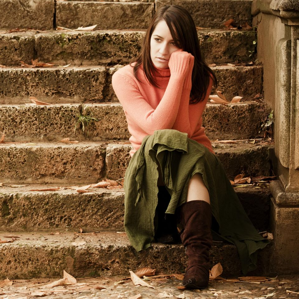 Wie ärgere ich mich weniger über andere? Eine nachdenkliche Frau sitzt auf einer Treppe