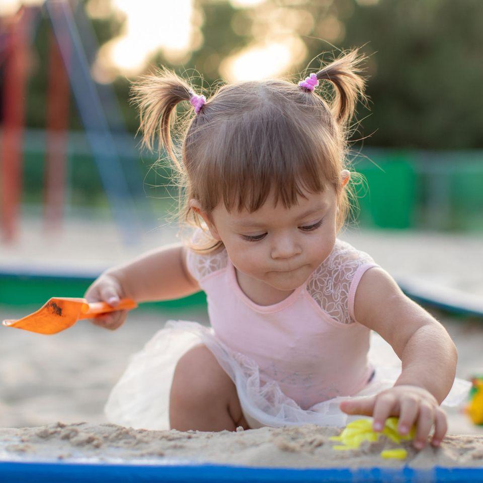 Zwischen Rutsche, Schaukel und Still-BH: Kind spielt im Sand