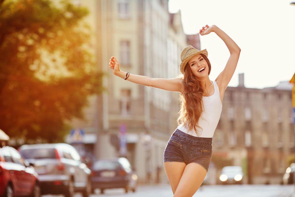 Horoskop: Eine glückliche Frau tanzt im Sommer