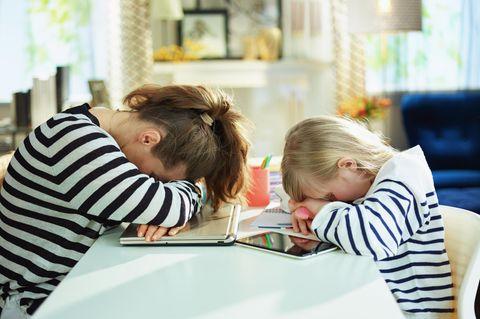 Homeoffice plus Homeschooling geht gar nicht: Mutter und Tochter legen Kopf auf den Tisch