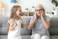 Trotz: Großmutter hält sich die Ohren zu während kleines Mädchen schreit