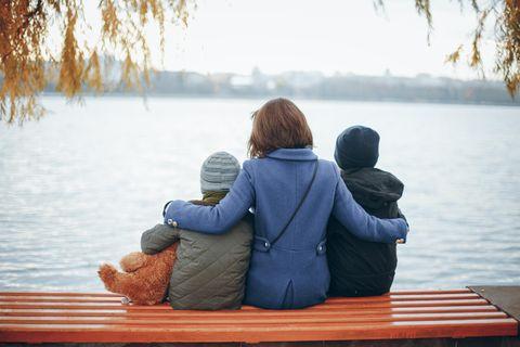 Mutterliebe: Frau mit zwei Kindern auf Bank