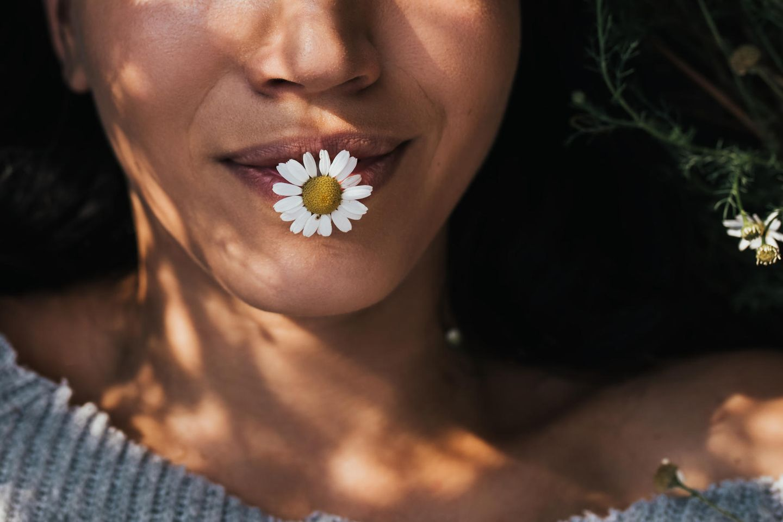 Wie kann ich meine Performance steigern? Eine entspannte Frau mit einem Gänseblümchen im Mund