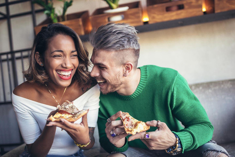 Pizza vom Vortag: Pärchen isst Pizza auf dem Sofa