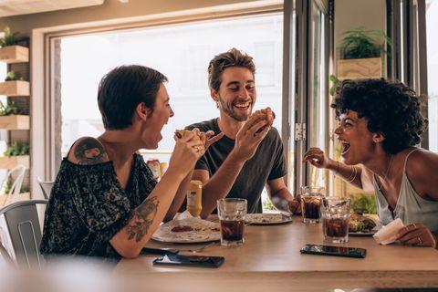 Fünfte Rad am Wagen: Drei Freunde sitzen am Tisch und Essen