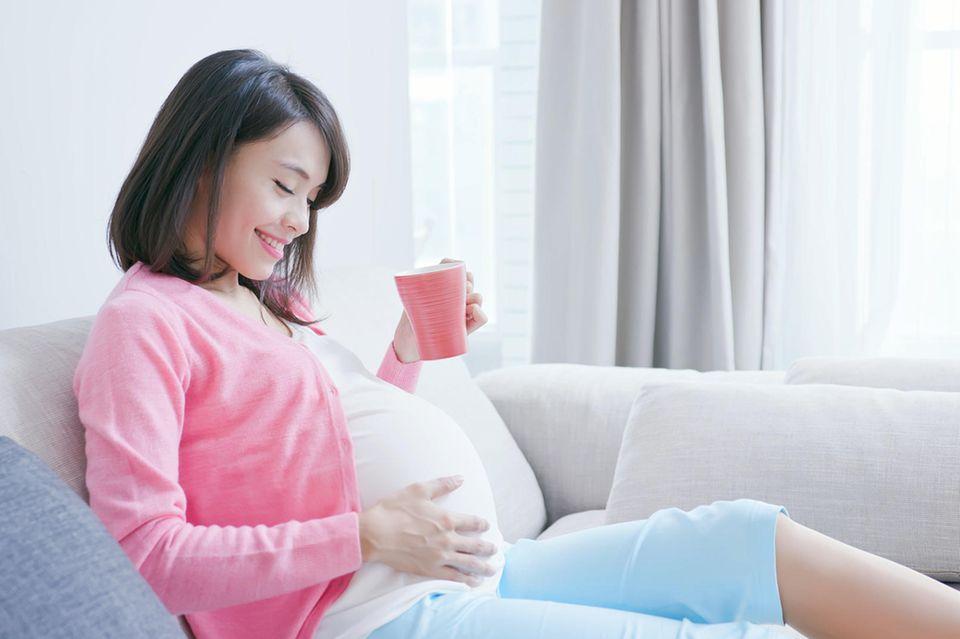 Weg mit den Schuldgefühlen!: Schwangere sitzt auf der Couch