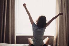 Morgenrituale erfolgreicher Menschen: Eine Frau sitzt auf ihrem Bett und streckt sich