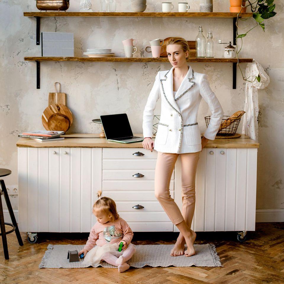 Gleichberechtigung: Frau mit weißem Blazer und Kleinkind