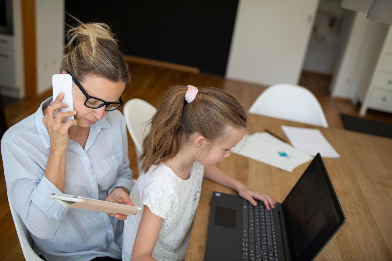 Home Office mit Kindern: Tochter auf Schoß der Mutter