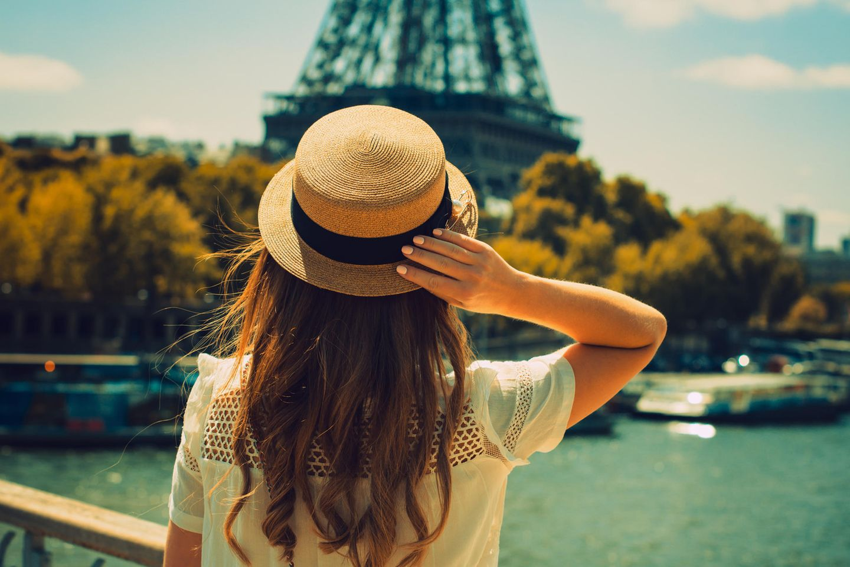 Paris-Syndrom: Eine junge Frau von hinten, die sich den Eiffelturm anschaut