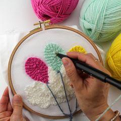 Punch Needle: Frau hält Punch Needle und Stickrahmen