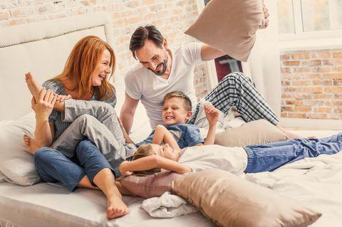 Vorteile des Elternseins: Familie macht Kissenschlacht im Bett