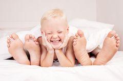 Familienbett: Kind liegt mit Eltern im Bett