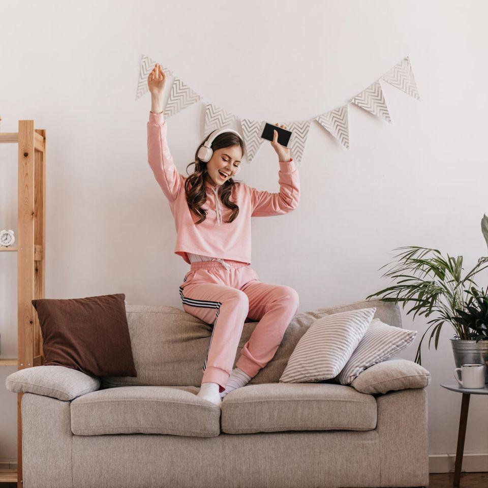 Jogginghose: Mädchen im Jogginanzug auf dem Sofa