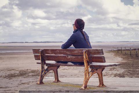 Guy Winch: Eine einsame Frau auf einer Bank am Strand
