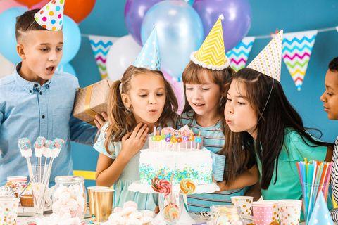 Kindergeburtstag: Kinder feiern und pusten Kerzen aus