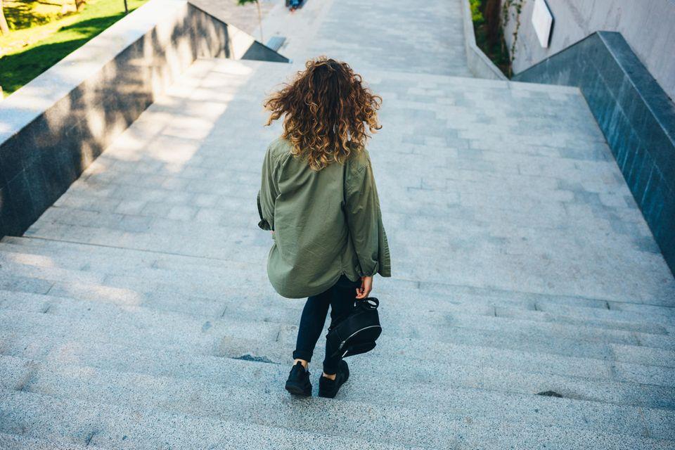 Bummeln: Frau geht Treppe herunter