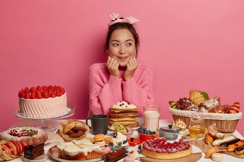 Dessertburger: Frau sitzt vor ganz viel Nachtisch