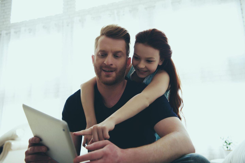 Krisenzeiten: Tochter mit Vater vor Laptop
