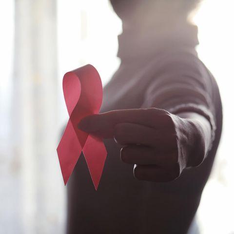 Brustkrebs behandeln: Frau hält rotes Band in die Kamera