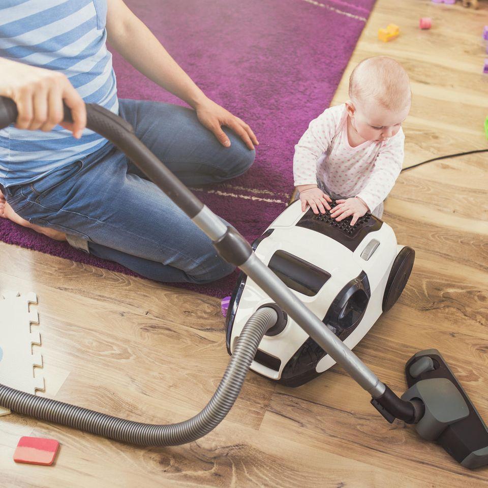 Hausmann: Vater staubsaugt mit Kleinkind